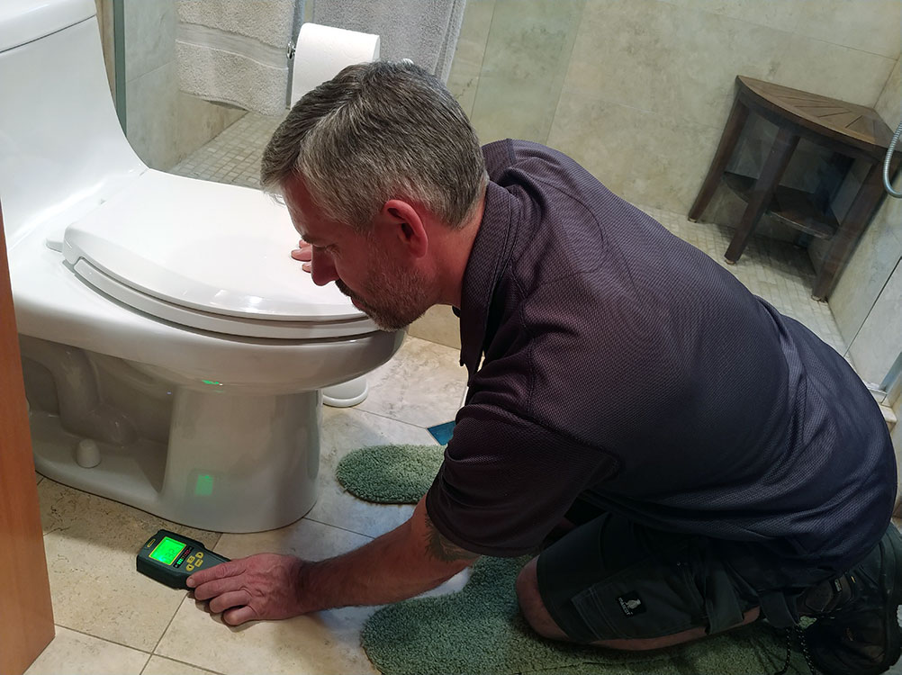 inspecting floor of bathroom